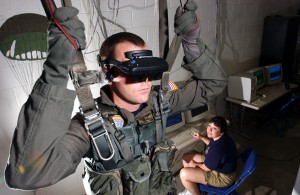 021115-N-5862D-001 Aboard Naval Air Station (NAS) Pensacola (Nov. 15, 2002) -- Hospital Corpsman 2nd Class Tim Sudduth, from Vashowish, Wash., demonstrates the Virtual Reality (VR) parachute trainer, while Aviation Survival Equipmentman 1st Class, Jackie Hilles, from Ekland, Penn., controls the program from a computer console.  Students wear the VR glasses while suspended in a parachute harness, and then learn to control their movements through a series of computer-simulated scenarios. The computer receives signals from the student as they pull on the risers that control the parachute. The VR trainer also teaches aircrew personnel how to handle a parachute in different weather conditions and during possible equipment malfunctions. Navy and Marine Corps aviators receive state of the art training at the Naval Survival Training Institute. U.S. Navy photo by Chief PhotographerÕs Mate Chris Desmond.  (RELEASED)